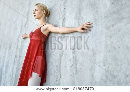 Delightful ballerina leans on the concrete wall with outstretched to the sides arms. She wears a red skirted leotard with light leggings. Girl looks forward. Sun shines onto her body. Closeup.