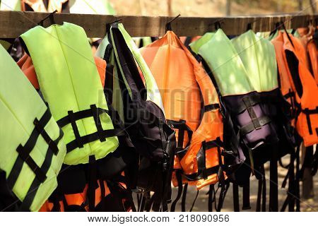 Colorful life jackets hanging on the row