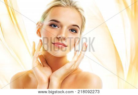 Attractive young girl touching her face on wavy orange background. Youth and skin care concept