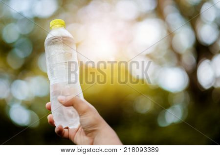 Hands holding a bottle of drinking water in the nature of natural drinking water.Man's hand holding drinking water bottle .Clean drinking water from natural .