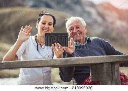 Smiling caregiver nurse and disabled senior patient using digital tablet outdoor