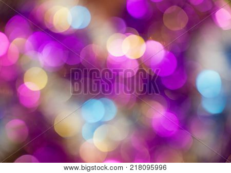 Beautiful bokeh of vivid round lights of changing slowly violet blue orange yellow pink and purple colors. Horizontal photo of colorful background