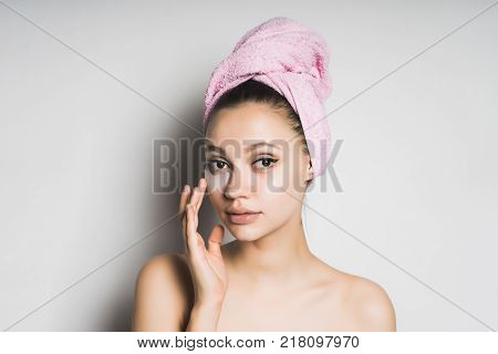 a young beautiful girl takes care of herself, on her head a towel, under the eyes of silicone patches