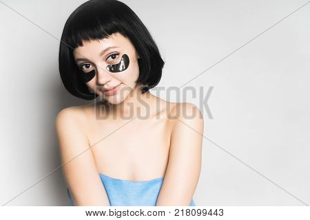 attractive young girl with clean skin and with short black hair looks into the camera and smiles, under the eyes black silicone patches