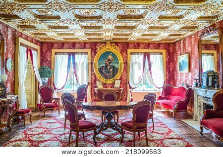 Venaria Italy - May 212017: The red living room with royal portrait in the Royal apartments of La Mandria castle