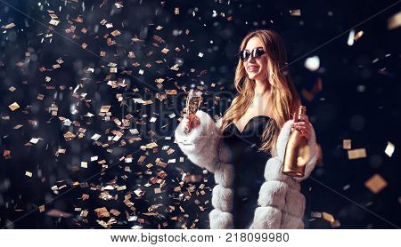 Well-dressed pretty woman in sunglasses drinking champagne and standing in falling snow and confetti.