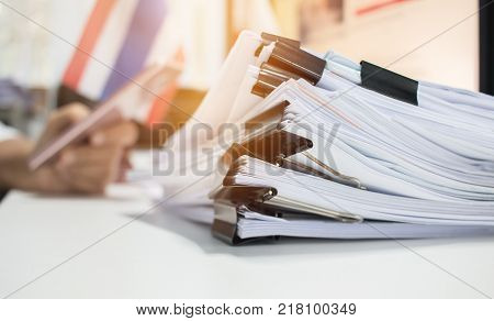 Paper stack Pile of unfinished documents on office desk related to business functions. Stack of business papers for Annual Report files on blur National flaguse smart phone. Business offices concept