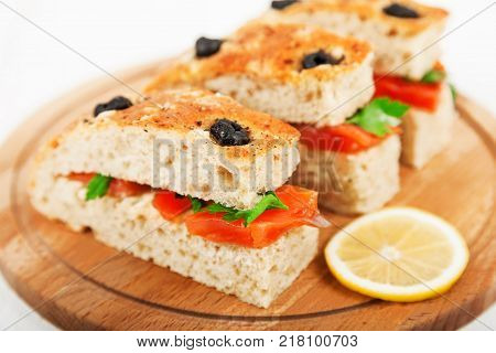 Delicious sandwiches with salted salmon and parsley closeup. Homemade whole wheat Focaccia with red fish