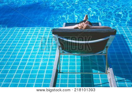 Relaxation Concept : Woman sleeping on outdoor daybed in swimming pool at the resort.