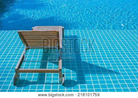 Relaxation Concept : Wooden daybed setting on mosaic tiles in swimming pool at the resort.