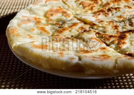 Hychin bread pie with potato stuffing. Traditional Caucasian cuisine - hot Ossetian pie.