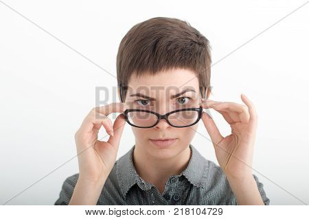 A young woman wearing glasses. Glasses woman showing eyewear happy holding glasses frame. Closeup of young caucasian woman.