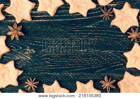 The horizontal Christmas background of blue vintage table, and cookies stars and star anise. Background with copy space