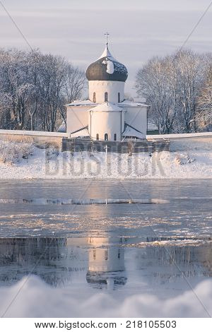 Vertical tonted purple shot of white stone Church reflected in the river. Winter landscape