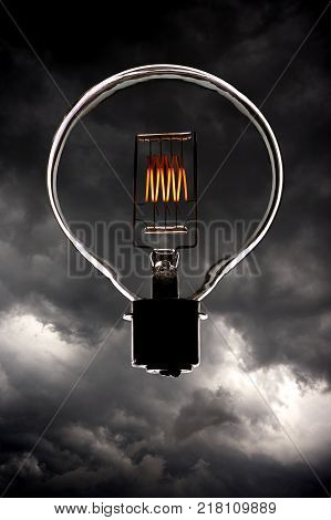 Electric Light Bulb With Glowing Filament Floating In Sky With Storm Clouds