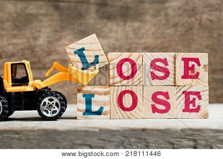 Yellow toy bulldozer hold letter block L to complete word lose lose on wood background