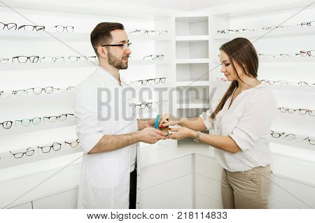 woman chooses eyeglasses to correct vision standing at ophthalmological store near shelf with many glasses. Consultant ophthalmologist helps the visitor to choose a frame for glasses.