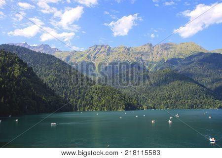 Beautiful panorama of natural mountain landscape. Pleasure boats on the water. Blue Lake Ritsa among mountains of the Caucasus, Abkhazia. Ritz Park poster