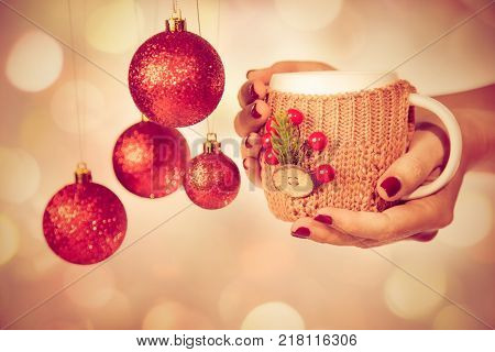 Close up of winter holiday cup in knitted vintage knitted cupholder with christmas decorations in hands of woman with beautiful festive red manicure and New Year hanging balls. Toned color photo.