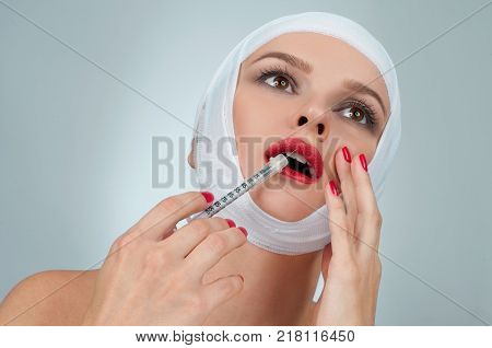 Woman with syringe. Beautiful woman after plastic surgery with bandaged face. Beauty Fashion and Plastic Surgery concept