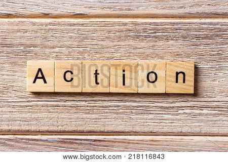 Action word written on wood block. Action text on table concept.