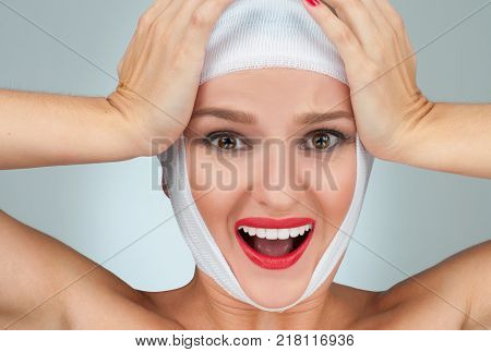 Woman has headache. Beautiful woman after plastic surgery with bandaged face.