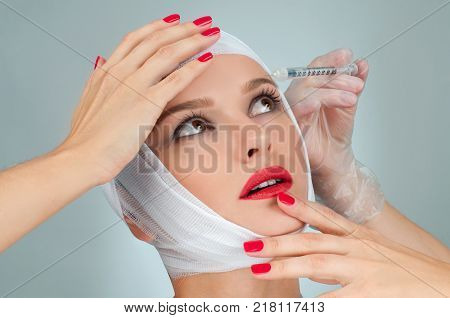 Woman get injection in lips. Beautiful woman after plastic surgery with bandaged face. Beauty, Fashion