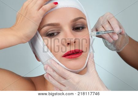 Patient in bandages getting injection over eyebrow.  Beauty, Fashion and Plastic Surgery concept