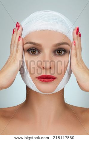 Beautiful woman after plastic surgery with bandaged face. Beauty