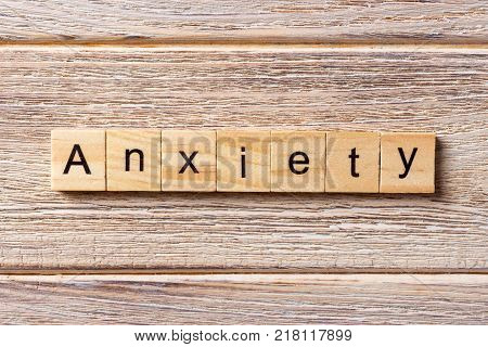 ANXIETY word written on wood block. ANXIETY text on table concept.