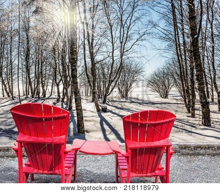 Bright winter frosty day. Large red plastic chaise lounges for relaxing. Sunset in the Arctic. The sun shines low over the horizon. The concept of extreme and ecotourism tourism