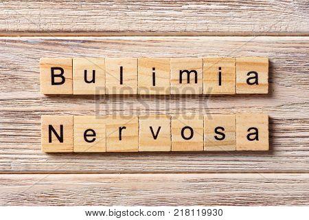 BULIMIA Nervosa word written on wood block. BULIMIA Nervosa text on table concept.
