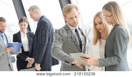 Business people team using a digital tablet and talking