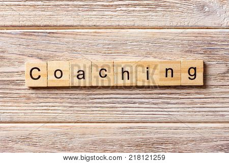 COACHING word written on wood block. COACHING text on table concept.
