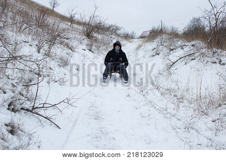 Teen rides on sledges from the mountain in winter