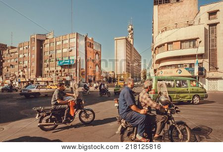 TEHRAN, IRAN - OCTOBER 6, 2014: People driving by cars motorbikes and taxi on street of iranian capital on October 6, 2014. With a population of 8.3 million Tehran is 32nd national capital of Iran