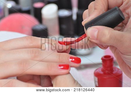 Women getting treatment at nail salon, Woman hands receiving a manicure in beauty salon.