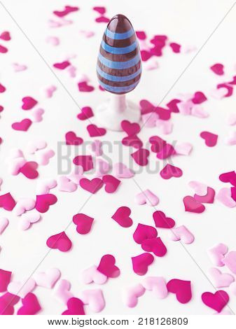 Ceramic butt plug with a pattern in blue and black stripes is on a white background with red and pink hearts made of cloth. Romantic background for Valentine's Day or for sex shop advertising