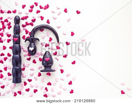 Various rubber sex toys (dildo, butt plug) are arranged on a white background with red hearts. Romantic background for goods from a sex shop or Valentine's Day