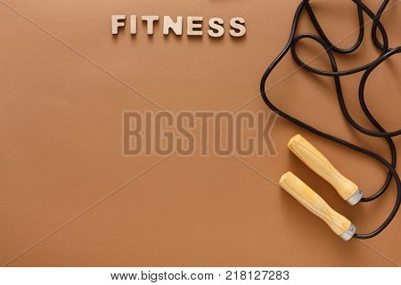 Fitness word and jumping rope on brown background. Skipping rope, sport supply, weightloss, slimming concept, top view, copy space