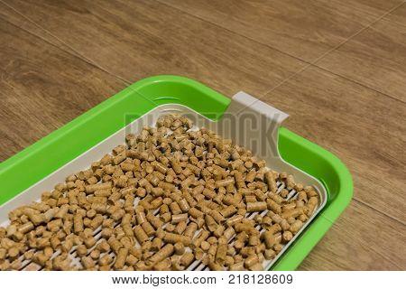 Cat's plastic toilet. Tray for pets. Wood filler. Horizontal rectangular photo.