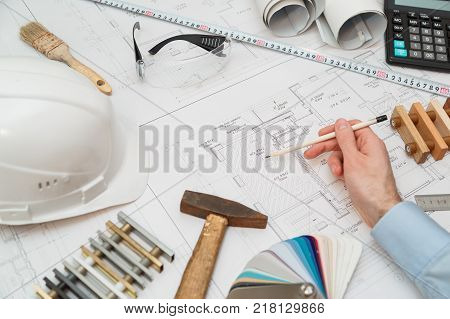 Concept architects or engineer holding pencil pointing equipment architects. On the desk with a blueprint in the office