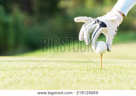 Asian woman putting golf ball on tee with golf club on sunny day for healthy sport. Lifestyle Concept.