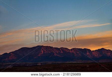 Glowing salmon mountaintops of St. George Utah during sunrise in Utah.