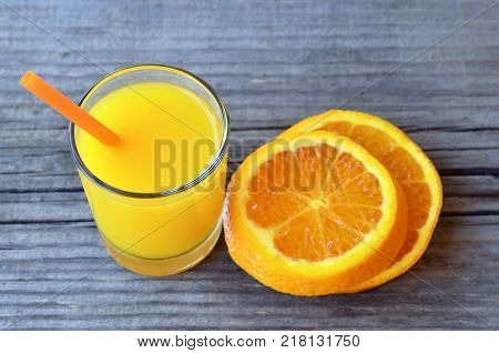 Glass of fresh orange juice and slices of orange fruit on rustic wooden table.Freshly squeezed orange juice with drinking straw and orange slices.