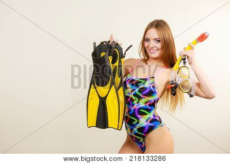 Woman fit body wearing swimsuit with mask tuba flippers snorkel having fun studio shot on grey. Happy joyful girl dreaming about summer vacation. Snorkeling swimming concept