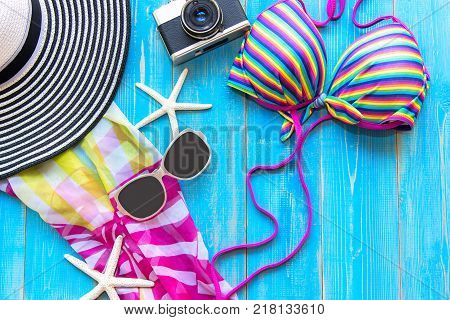 Summer Fashion woman swimsuit Bikini camera fish star sunblock sun glasses hat. Travel in the holiday wood blue background. Summer Concept.