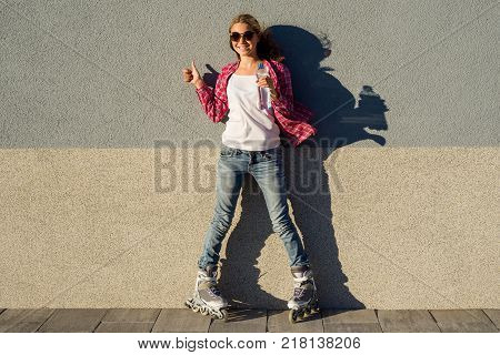 Portrait of young cool smiling girl shod in rollerblades, holding a water bottle and showing a thumbs up. Thumb up health and sport