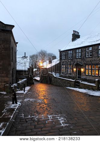 the village of heptonstall in the snow at night with lamps shining onto the cobbled road at twilight