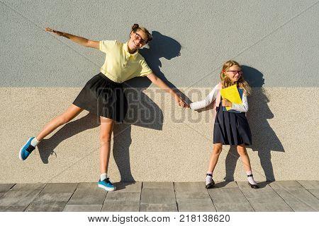Cute sisters schoolgirls in school uniform. Schoolgirls in glasses, together enjoying outside